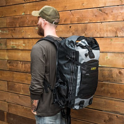 Side Back View of Man Wearing Nelson Rigg Hurricane Waterproof Backpack & Tailpack on Back